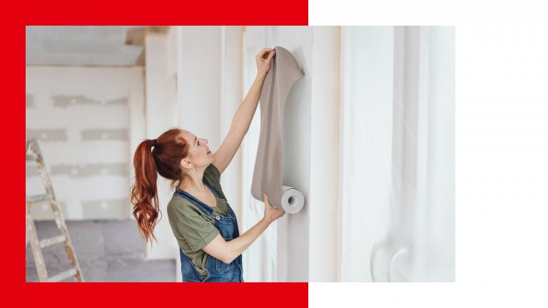 Eine Frau tapeziert ihre Wohnung.